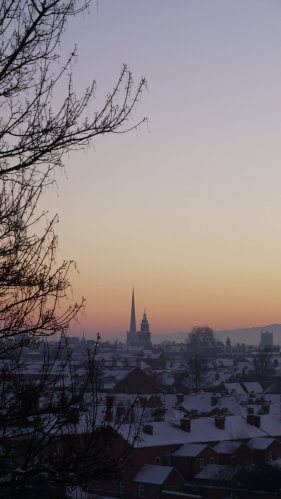 Snow covered rooftops, hazy sunset, framed to one side by the silhouette of a tree.