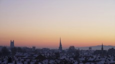 A snowy winter sunset photo looking across the city rooftops towards the Malvern Hills.