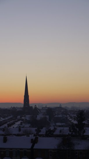 Snow covered rooftops in Worcester with a church spire silhouetted against the sunset.