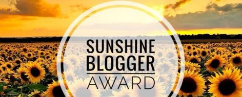 Sunshine Blogger Award Logo featuring a huge field of bright yellow sunflowers bathed in golden sunshine.