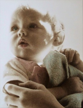 A delicate photo of a baby being held and looking to one side. The photo has been chemically sepia-toned. The baby's eyes and blanket have been hand-tinted blue, her mouth and clothing pale pink.