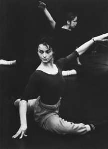 Black and white photo of a female ballet dancer in rehearsal. She's sat on floor in a ballet position with one arm outstretched. There is another dancer just out of focus behind.