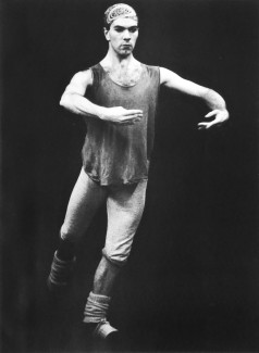 Black and white photo of a male dancer against a dark background. He is wearing a loose shirt, leggings and a bandana. A focused expression on his face as he holds a simple ballet position.