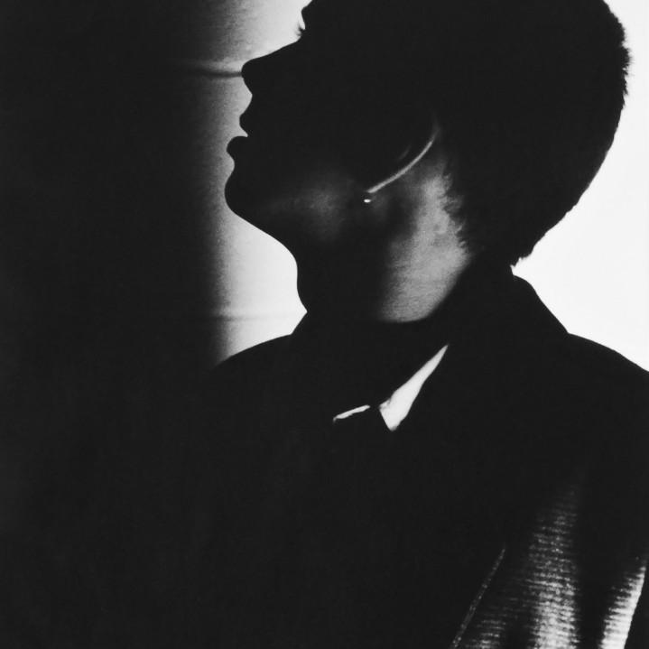 Stylish head and shoulders black and white shot of a guy with a flat-top hair cut. Photo is sparsely lit. Subject is almost silhouetted and is looking towards left of photo which is in total shadow.