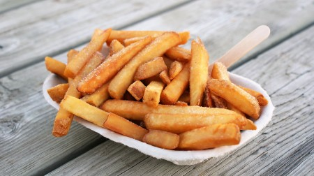 A tray of chips with a wooden fork, on a wooden bench.