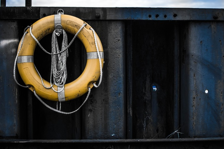 A pale yellow lifebelt with rope attached to the side of a dock.
