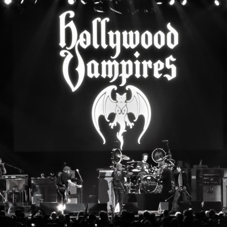 Black and white photo of the Hollywood Vampires on stage with giant Hollywood Vampire logo backdrop.