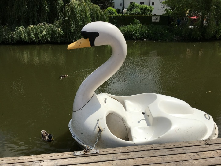 A delapidated swan shaped pedalo floating on a lake, tied to a mooring.