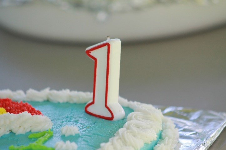 A red and white number one birthday candle on top of a blue and white iced cake.
