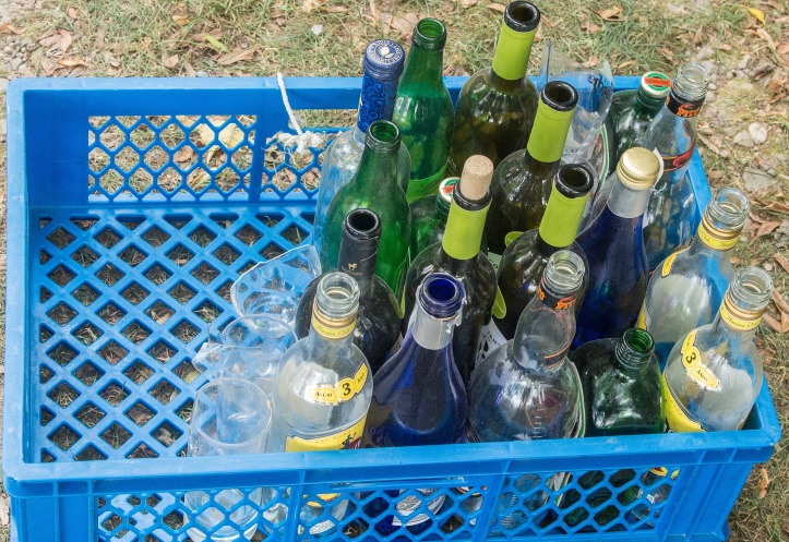 A blue plastic crate holding a variety of empty alcohol bottles.