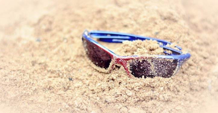 Red and blue sunglasses, covered in sand, on a beach.