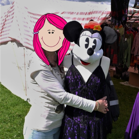 I'm standing with my arms round a mannequin that is wearing a Minnie Mouse face mask and a long purple dress. My identity is hidden behind a cartoon face with pink hair.