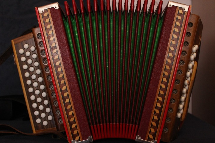 An accordion. Wooden box with white buttons, red trim and green detail.