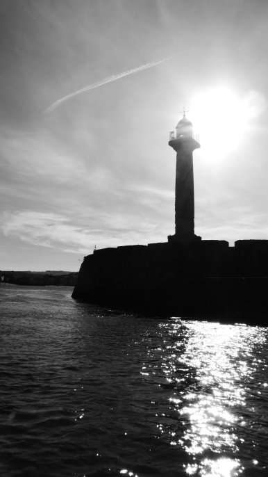 A dramatic black and white view of the sea and a lighthouse. The sun is glaring brightly, looking as though it is being emitted by the lighthouse.