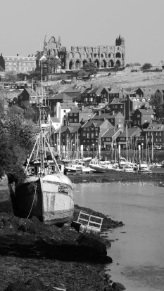 Black and white photo of a river estuary. In the foreground to the left is a large grounded boat. Behind are several boats in a marina, framed by houses and Whitby Abbey rising above in the distance.