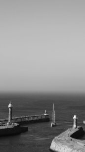 Black and white photo looking out to sea from a high viewpoint. Two piers with lighthouses fill the lower foreground. The sea and mist merge giving an eerie greyscale effect.