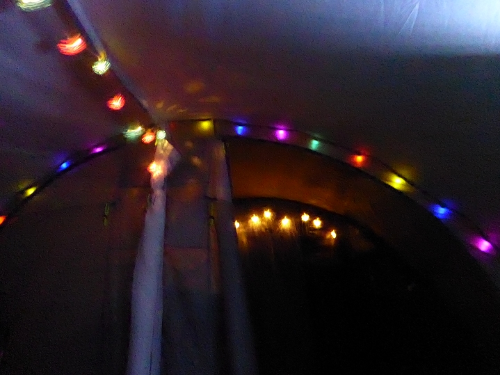 The inside of our tent, with 3 strings of brightly coloured lights, blurred by the motion of the tent being battered by the wind.