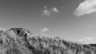 Black and white photo of a grassy hill with a dirt path leading to a pillbox fortification. Shot against a sky with a few clouds.