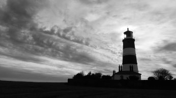 Black and white landscape photo of a striped lighthouse almost silhouetted against a dramatic cloudy sky.