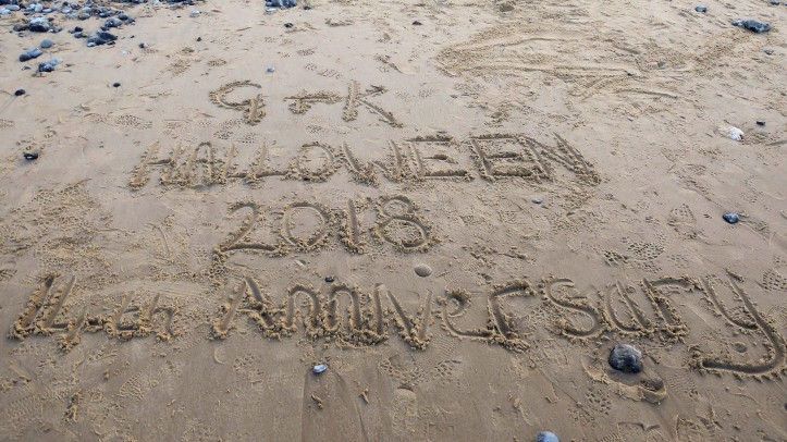 Message written in the sand on a beach saying 'G + K Halloween 2018 14th Anniversary'.