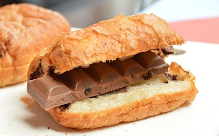 A croissant, halved and filled with a chocolate bar.
