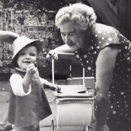 Black and white photo of me as a toddler with my Grandma. We are both kneeling in a backyard, with a toy pram between us. I'm wearing a dress and straw hat. My Grandma is in a spotty dress and smiling at a sweet I'm holding.