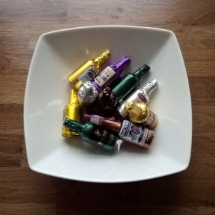 A white dish filled with colourful foil-wrapped bottle-shape chocolate liqueurs.