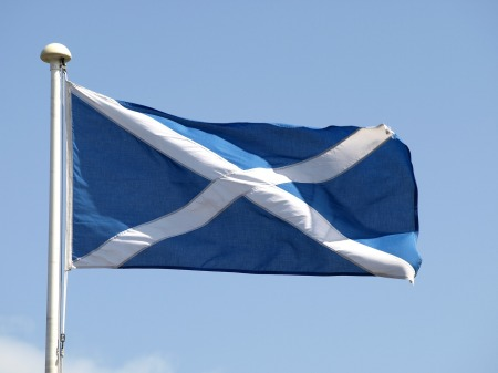 The Scottish flag flying from a flagpole against a blue sky.