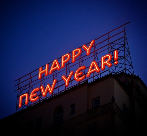 Large red neon sign above a building, against a twilight sky, saying 'Happy New Year'.