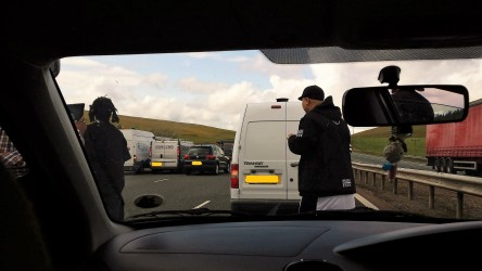 Photo taken through windscreen with Public Enemy/Entourage and halted cars on motorway.