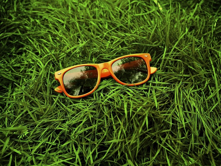 A pair of folded orange-framed sunglasses laying on grass.