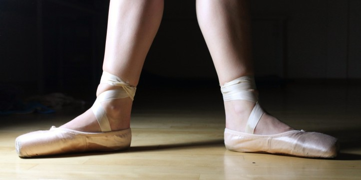 Lower legs and feet wearing pink satin ballet shoes tied around the ankles with ribbons.