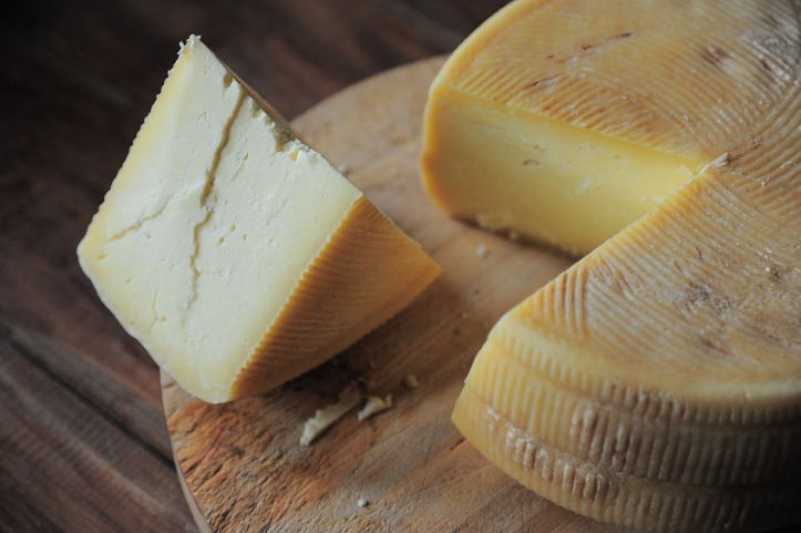 A wheel of yellow cheese on a wooden board, with one large wedge cut out and resting to the left