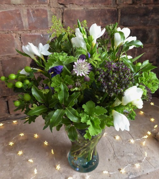 Photo of large bouguet in a glass jar set in a brick hearth. The flowers include white freesias, purple campanulas, astrantia, alliums and a variety of green foliage.