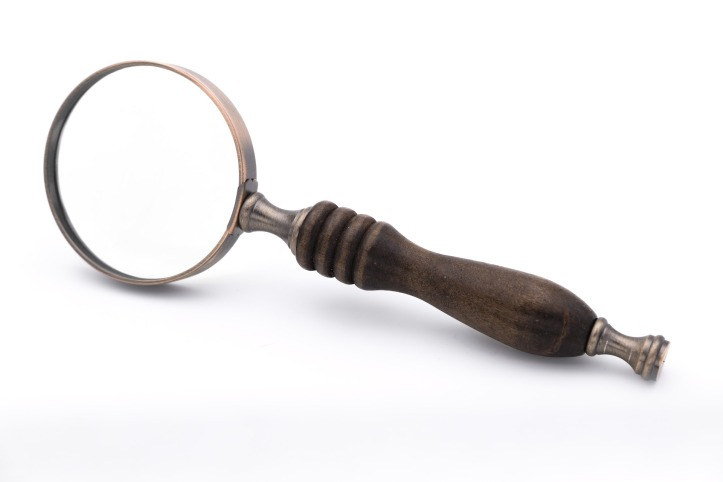 A large old-fashion handheld magnifying glass, propped onto its side.