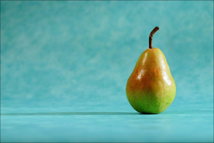 A single green pear with a partial red hue, set against a turquoise blue background.