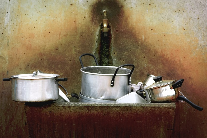 A very dirty old sink with a single tap. It's filled with an assortment of aluminium cooking pots and pans.