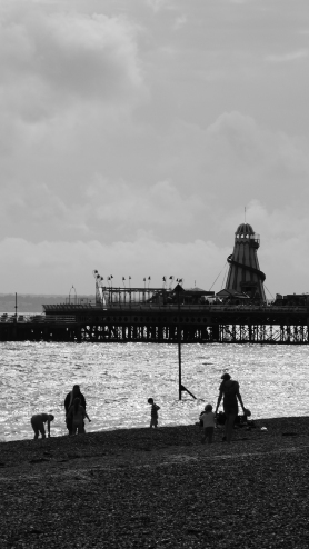 Black and white photo of a stone beach looking towards the sea and the end of a pier. There are silhouetted figures on the beach engaged in a variety of seaside activities. There is a helter-skelter and flags on the pier, set against a cloudy sky.