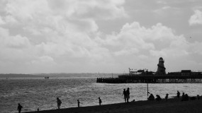 Black and white photo of a wide silhouetted beach scene. There are figures on the beach and a helter-skelter on a pier which is jutting out to sea. In the hazy distance are the hills of an island, all under a cloudy sky.