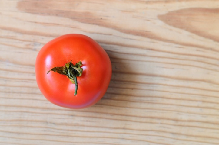 A single red tomato, viewed from above. It's sat on a light wooden worktop.