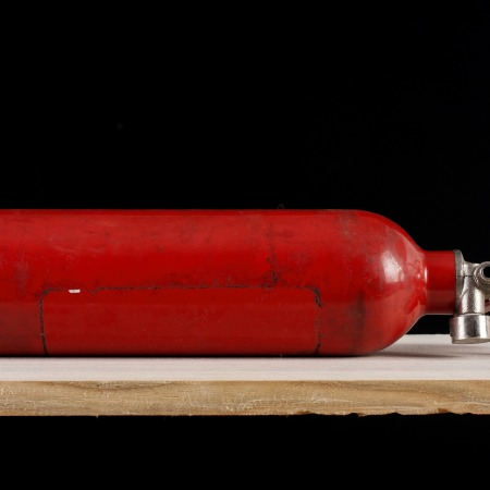 An old red, unlabelled fire extinguisher, lying on its side on a wooden table.