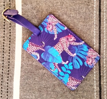 Purple, turquoise and pink rectangular luggage label with a buckle strap. The design is a jungle theme with jaguars and large palm-like leaves.