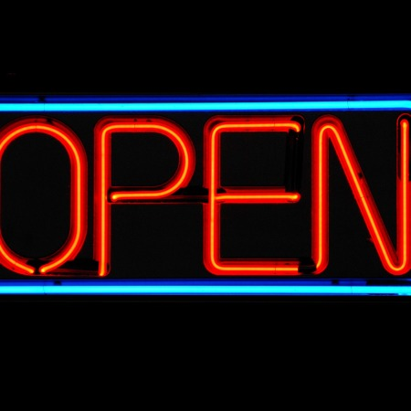 A red neon open sign, bordered by a blue neon line, set against a black background.