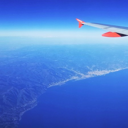 View through plane window looking down on Genoa and the edge of The Alps. The wingtip is visible against a hazy blue sky. Deep blue sea takes up the bottom right corner.