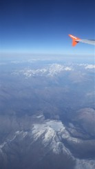 View from plane window overlooking The Alps. The plane's wingtip can be seen on the top right corner.