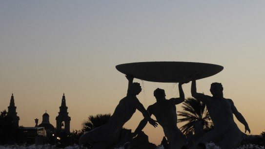 Silhouetted fountain against a pale sunset sky. The fountain comprises three Tritons (Mermen), holding aloft a large basin. To the left is the silhouette of a church and its bell towers.