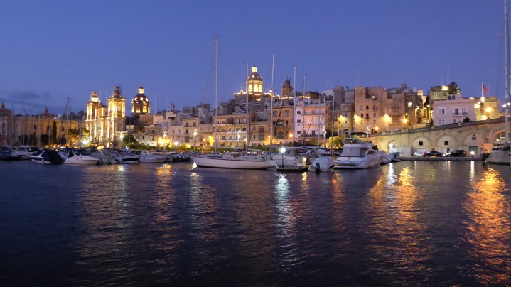 View from ferry back to harbour and marina at dusk. Yachts in the foreground against a backdrop of lit buildings and churches. Their lights are reflected in the water.